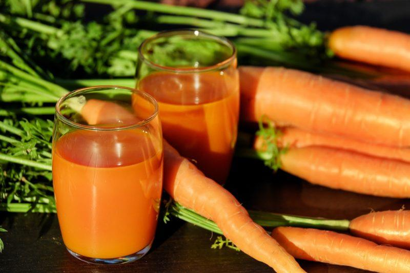 two glasses of carrot juice surrounded by carrots to represent where to buy fresh juice online