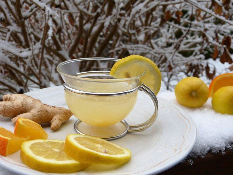a glass of lemon water on a plate surrounded by lemon slices to represent where to buy fresh lemons online