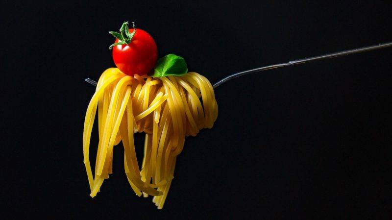 some pasta wrapped around a spoon with a small tomato on top to represent where to buy fresh pasta online