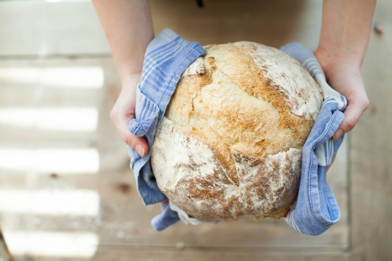 Someone holding a loaf of freshly baked bread to represent where to buy fresh yeast online