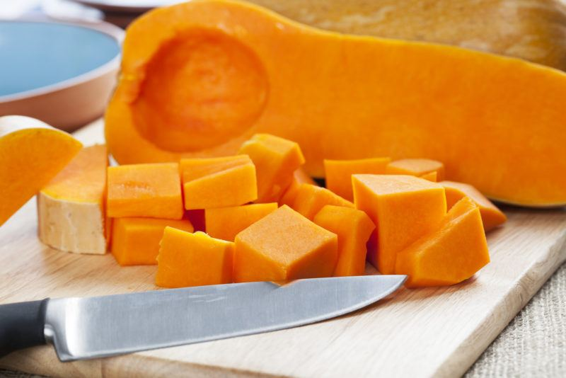 close up shot of butternut squash, half cubed while the other is just peeled