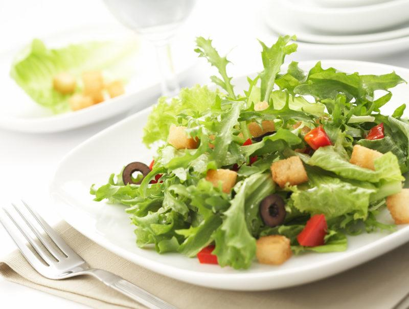 some leafy green vegetables and bell peppers on a white plate