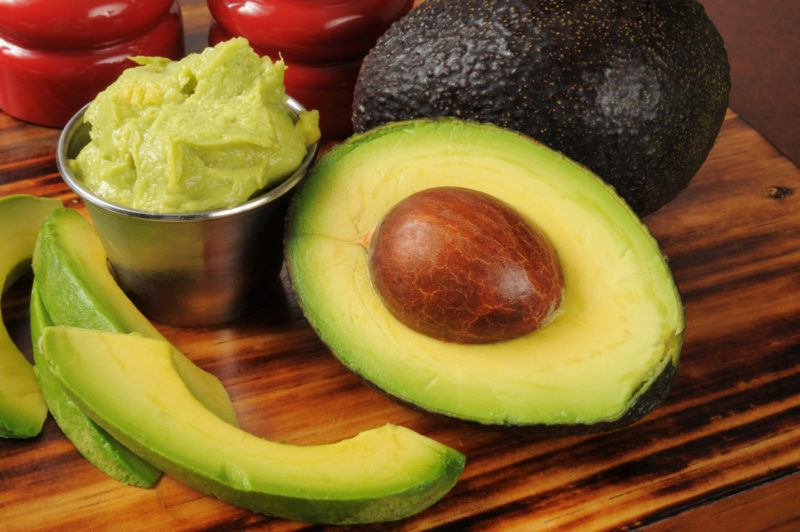 avocados on a table, some mashed, some whole, some sliced and peeled