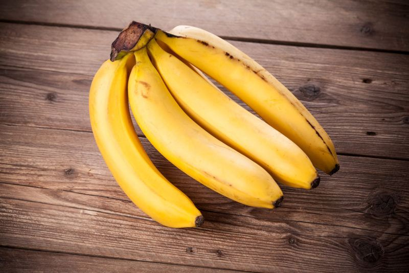 four ripe bananas still attached to their stems, placed on top of a wooden table