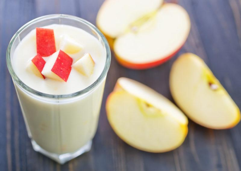 a whole glass filled with fresh yogurt, topped with some cubed and unpeeled apples, and more cut apples scattered around