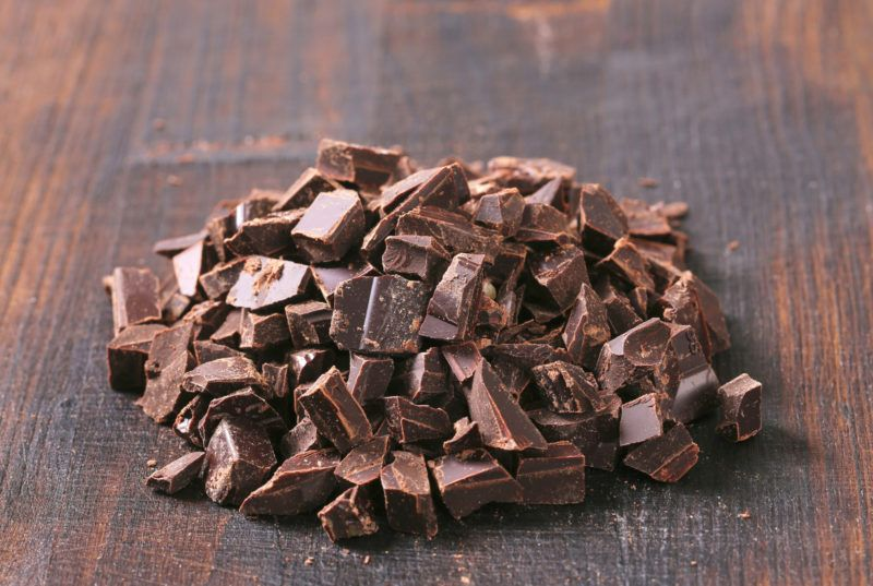 closeup shot of a bar of dark chocolate that has been chopped into bite-sized pieces