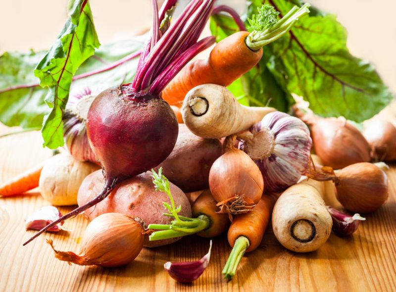 carrots, beets, onions, and more on a wooden table