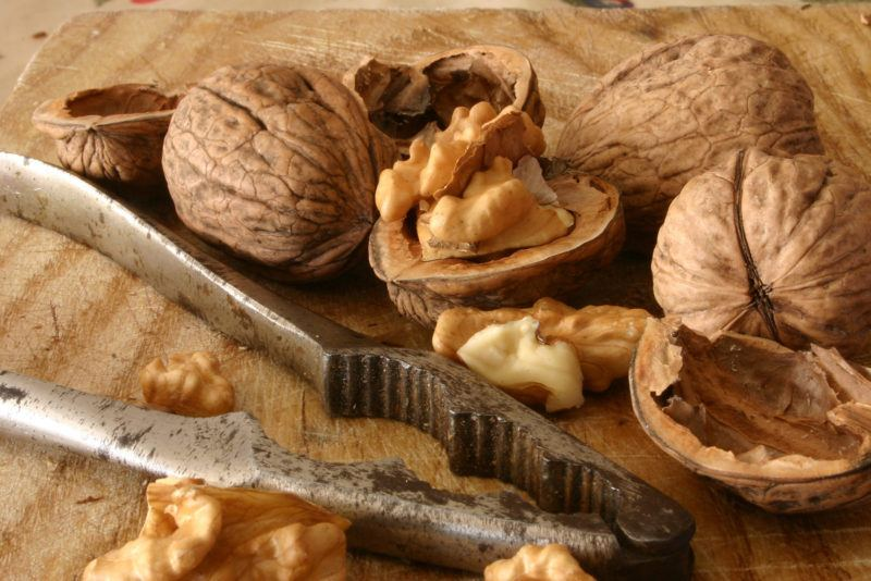 whole walnuts plus some cracked walnuts and a nutcracker on a table