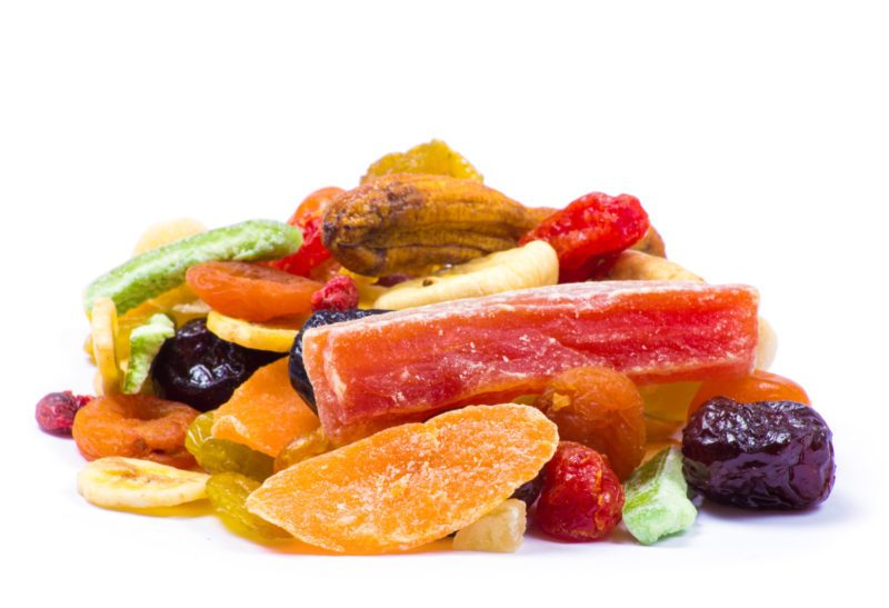 some dried raisins, oranges and many more on a white background