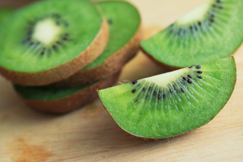 closeup shot of unpeeled, sliced kiwi on a wooden table