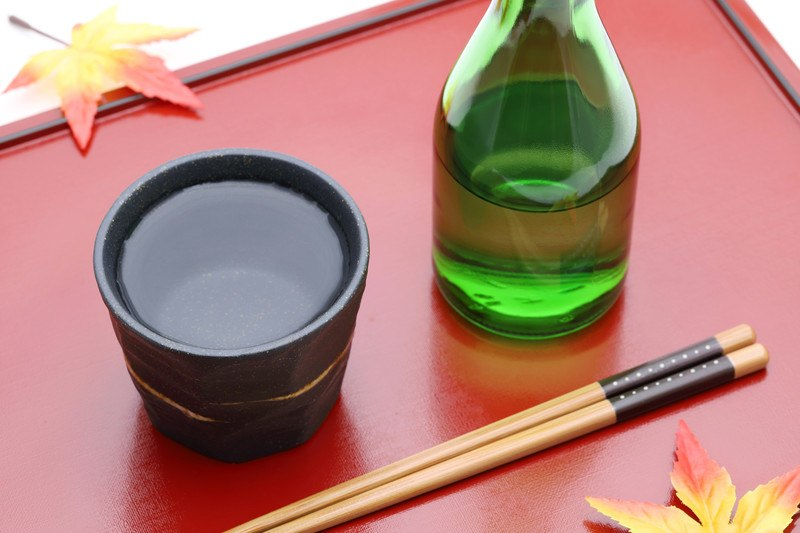 Bottle of sake and ceramic cup on wooden red tray, on white background with two fake leaves set on the edge of the tray  and a pair of chopsticks laid in front