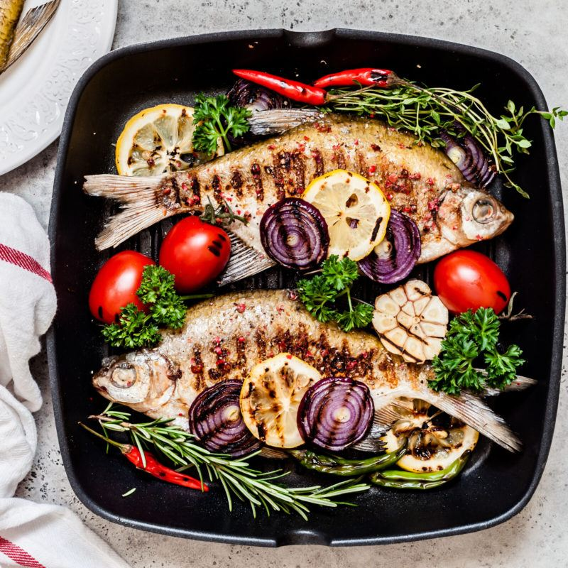 pan fried fish with red tomatoes, onion, red peppers and herbs resting in hot skillet removed from its base