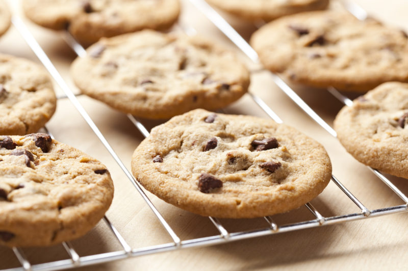 Fresh chocolate chip cookies on a cooling rack.