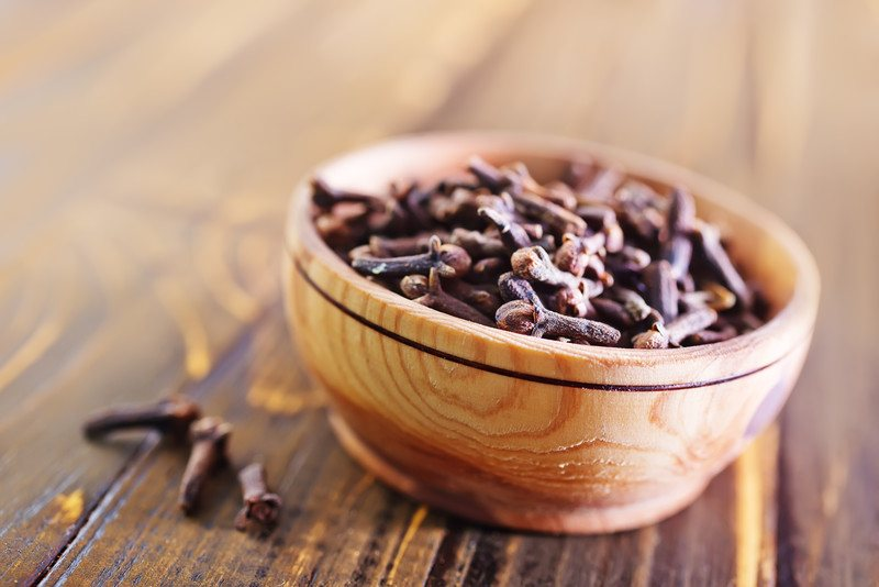 on a wooden surface is a closeup image of a wooden bowl full of cloves with 3 cloves beside it