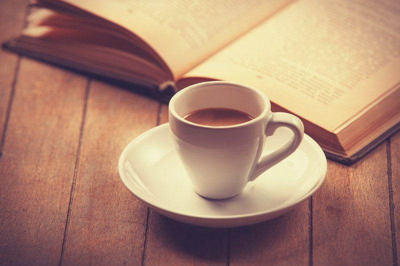 coffee cup with espresso in front of book