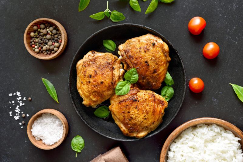 three cooked chicken breasts topped with basil on a black bowl, a bowl of peppers and salt, and a bowl of rice on a dark background
