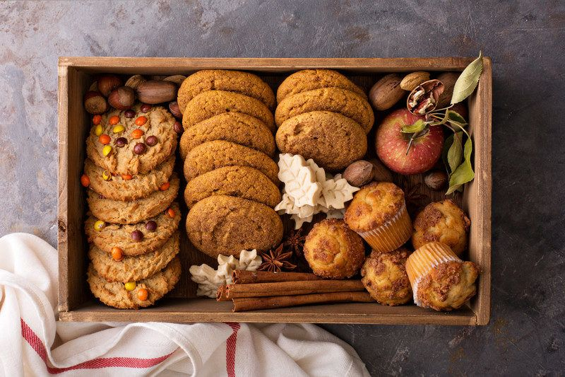a wooden box in autumn style with a variety of cookies and cupcakes inside