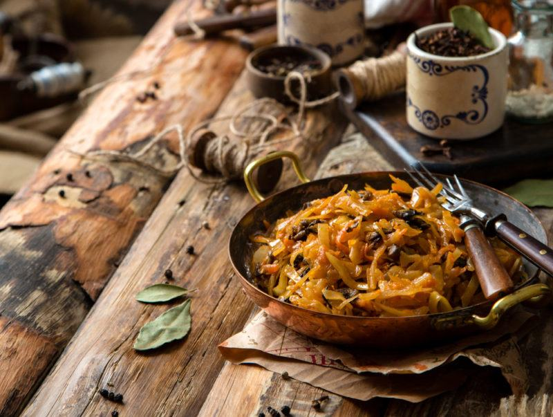copper skillet with onions and vegetables in rustic background