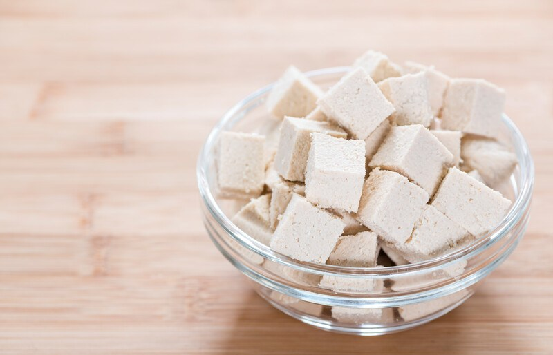 on a wooden surface is a glass clear bowl full of cubed tofu