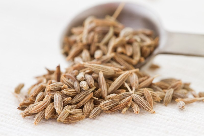 on a white table napkin is a closeup image of cumin seeds pouring out of a metal measuring spoon