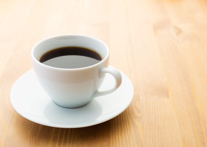 on a brown wooden surface is a white cup and saucer with black coffee in it