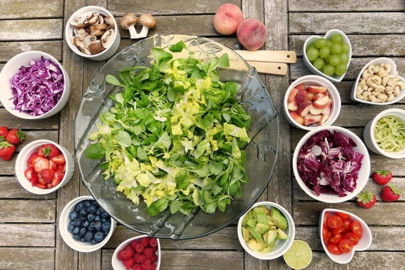 a bowl of salad surrounded by several other bowls of fruit to represent diet food delivery services