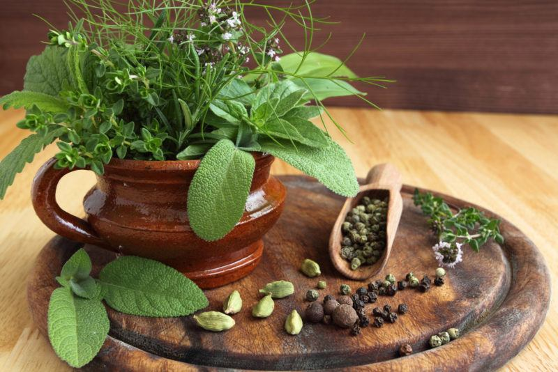 pepper, pergano, other herbs on a ceramic pot, placed on top of a circular wooden serving tray