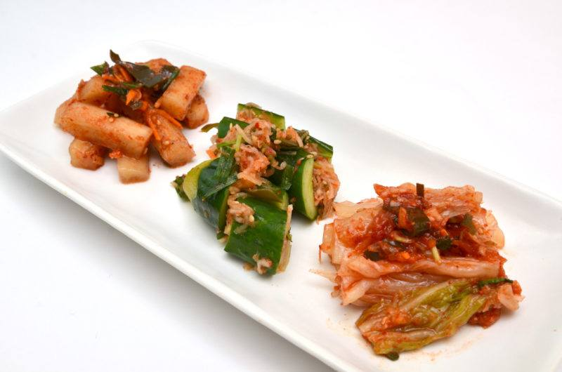 a plate of radish, cabbage, and cucumber kimchi on a white plate.
