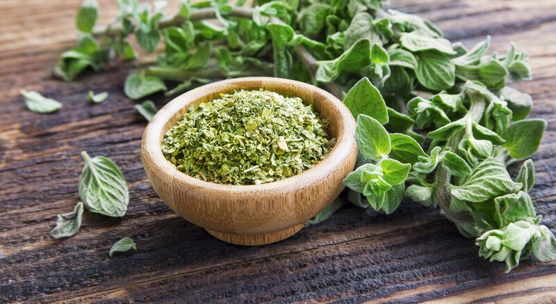 on a dark wooden surface is a wooden bowl full of dried oregano with fresh oregano leaves at the back