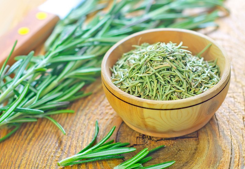 on a wooden surface is a wooden bowl full of dried rosemary with fresh rosemary herbs around it