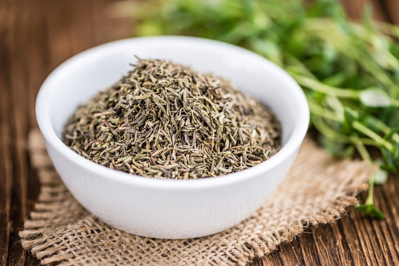 closeup image of a white bowl full of dried thyme on a burlap sack with fresh thyme at the back
