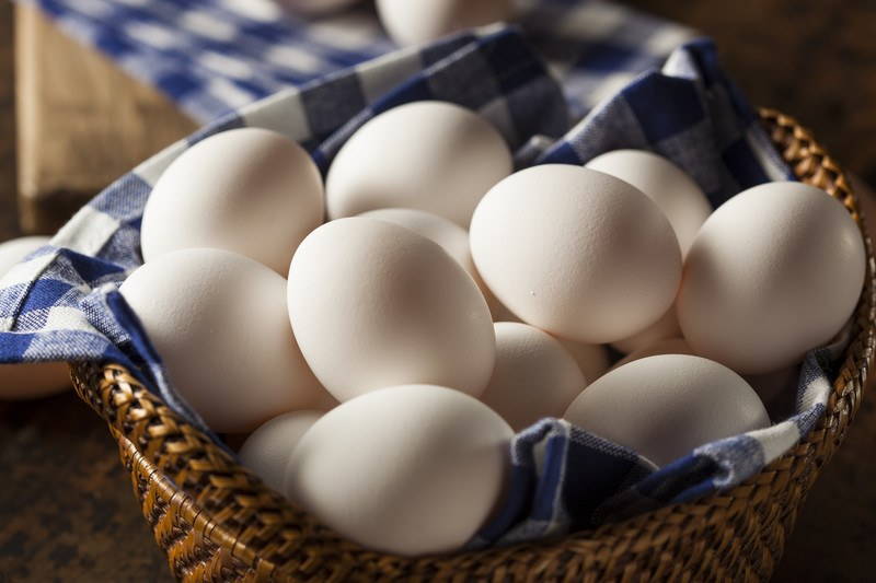 Several white eggs rest on a blue and white cloth inside a brown wicker basket.