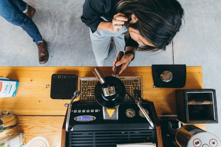 Photo from above - a woman at an espresso machine learning to make espresso