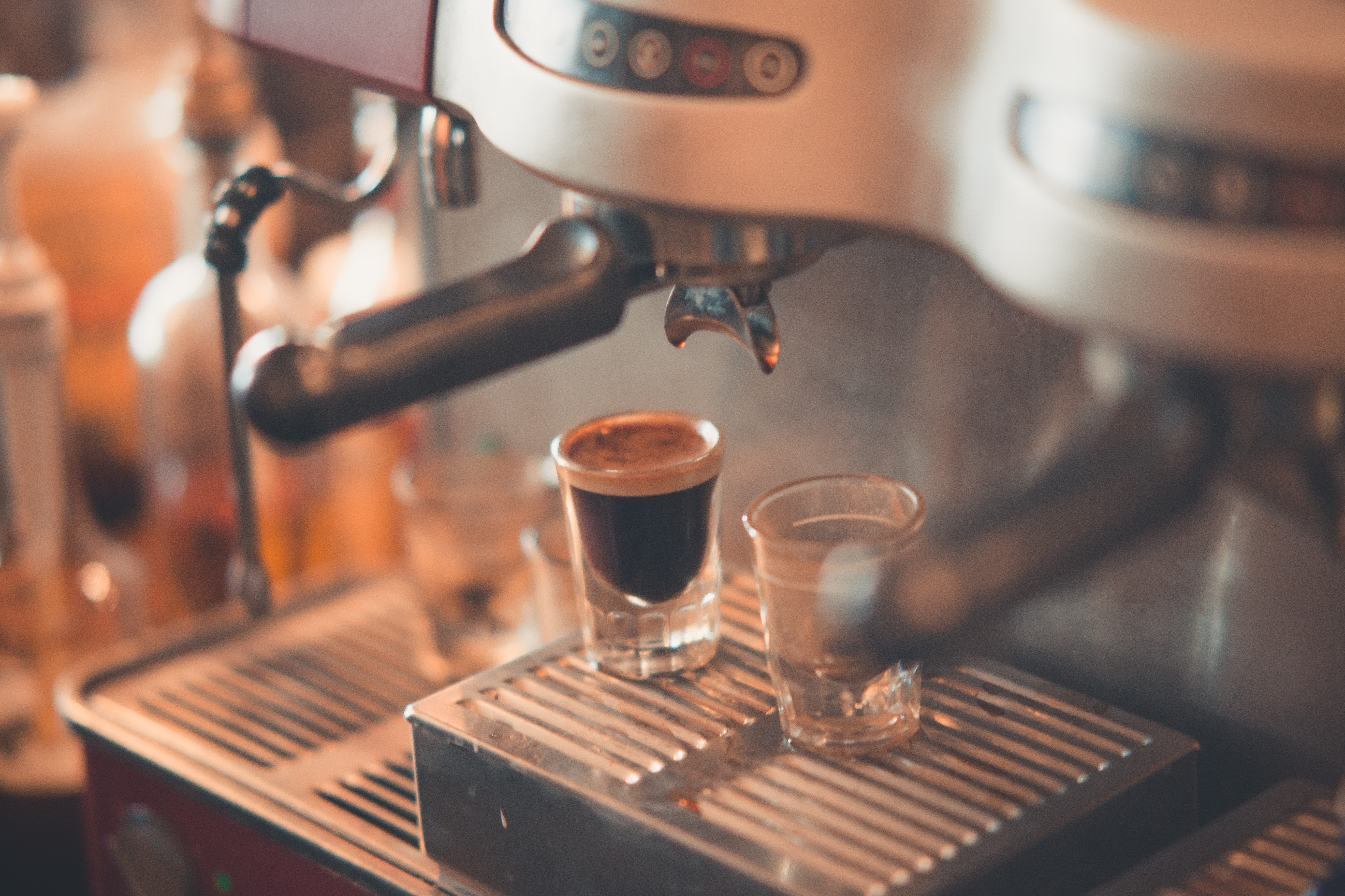 Filtered photograph of a large espresso machine with two shots under the spouts, one full of espresso and one empty
