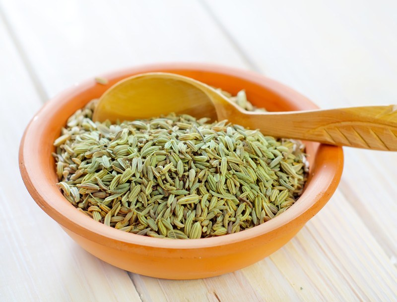 on a white wooden surface is a brown ceramic bowl full of fennel seeds with wooden spoon