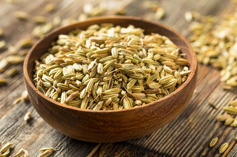 on a wooden surface is a brown wooden bowl full of fennel seeds with loose fennel seeds around it