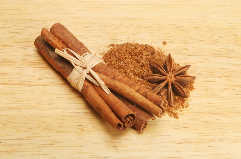 on a light-colored wooden surface is a bundle of cinnamon sticks, star anise, and a mound of five-spice