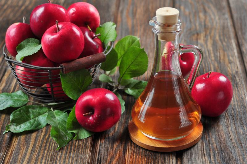 fresh red apples in a wire basket and a glass container filled with apple cider on a wooden table
