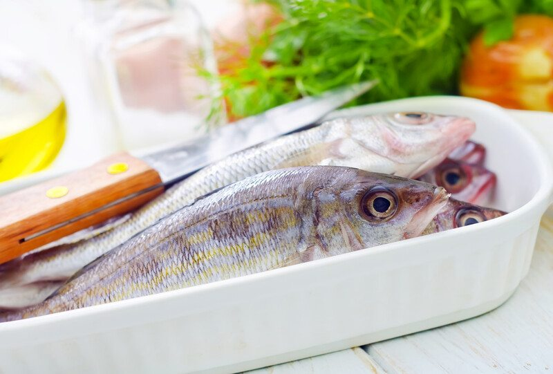 closeup image of a white ceramic dish with fresh whole fish, a knife and fresh herbs can be seen at the background