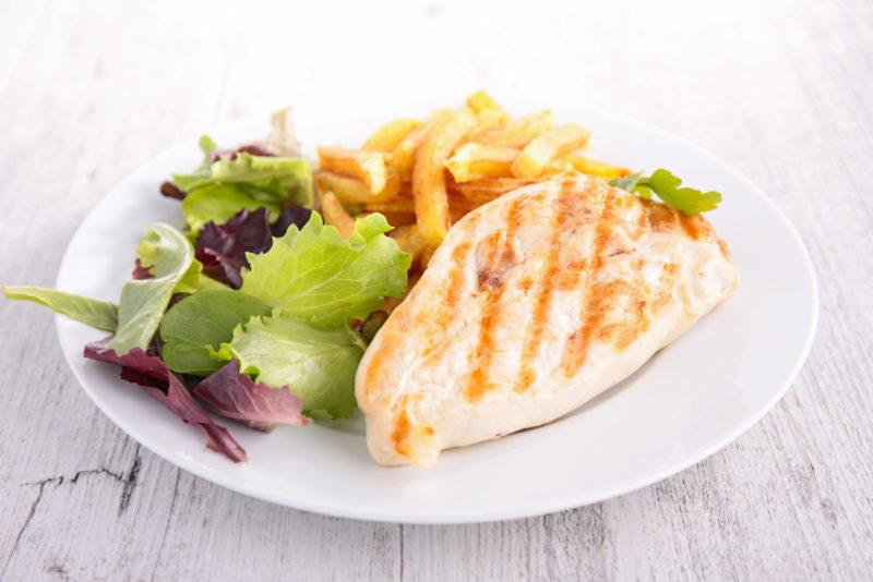 grilled skinless chicken breast served with salad and French fries.