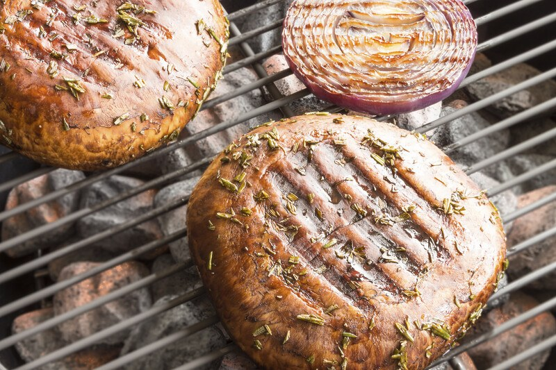 on a grill is a couple of Portobello mushrooms and a sliced red onion with visible grill marks and chopped herbs on top