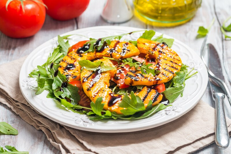 a beautifully plated grilled squash with herbs, greens, and balsamic dressing, plate is resting on a brown table napkin with knife and fork beside it and a couple of tomatoes and olive oil at the back