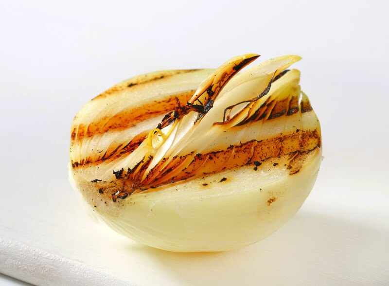 a closeup shot of a grilled white onion with grill marks