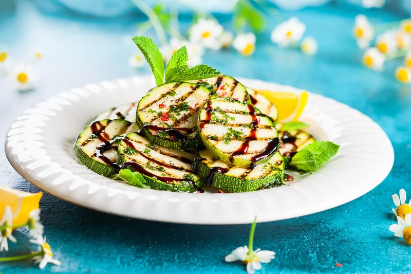 on a blue surface is a beautifully plated grilled zucchini with a sprig of herb and white little flowers around the white plate