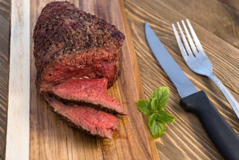 grilleld top sirloin steak with pepper crust on wooden board