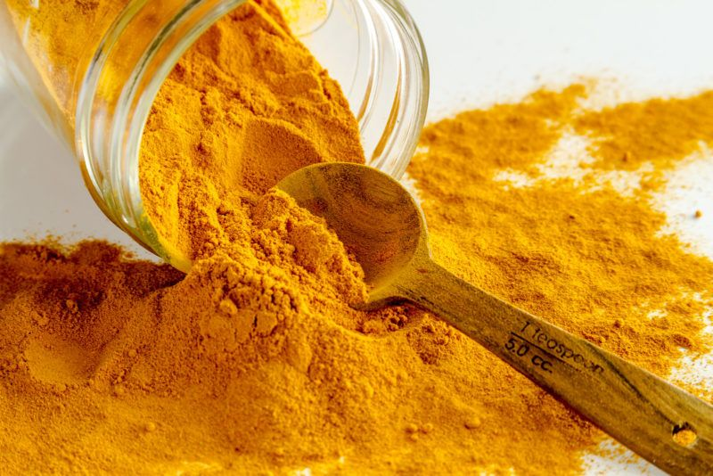 ground turmeric in a glass jar that has been tipped over