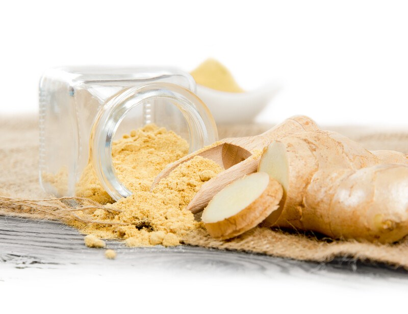 a little glass jar toppled over a burlap sack with ground ginger spilled from it, with wooden scoop also with ground ginger, fresh ginger root, and white bowl with ground ginger at the back