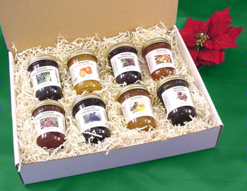 8 jars of jams and jellies displayed in a white shipping box packed in shredded raffia.