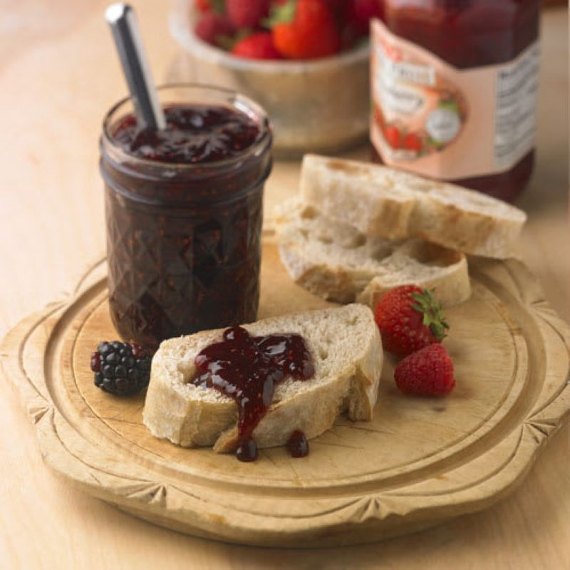 Jar of Jam with knife sticking out, sitting on a wooden plate with sliced baguette, fresh berries, and one of the pieces of bread has a small dollop of jam on it.  In the background are berries and another jar of jam