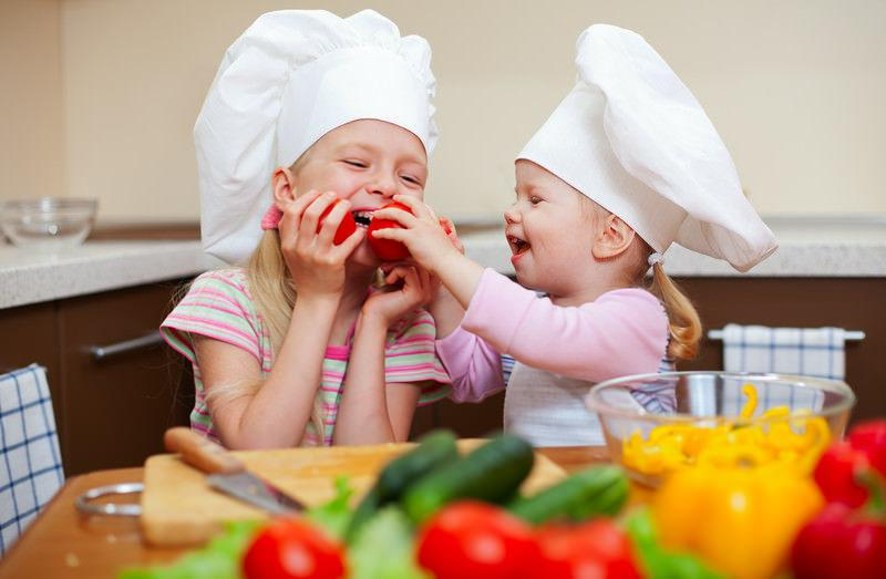 two young girls in the kitchen with chef hats preparing to make a meal with peppers, cucumbers